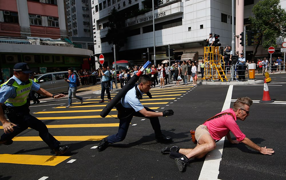 Police officers stop a pro-democracy protester, right, crossing the cordon line during a rally to promote the Hong Kong electoral reform in Hong Kong.