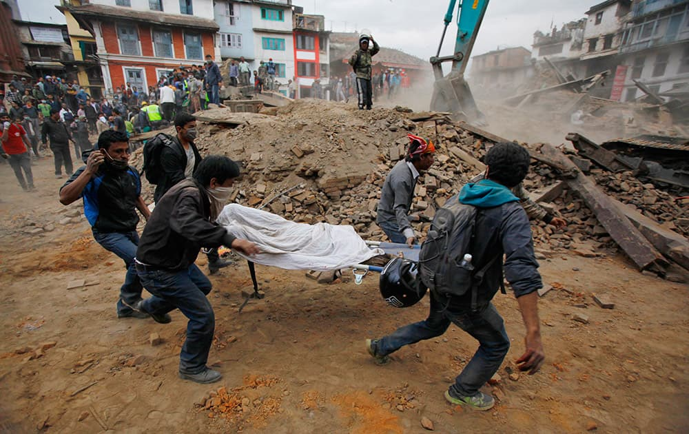Volunteers carry the body of a victim on a stretcher, recovered from the debris of a building that collapsed after an earthquake in Kathmandu, Nepal. A strong magnitude-7.9 earthquake shook Nepal's capital and the densely populated Kathmandu Valley before noon Saturday, causing extensive damage with toppled walls and collapsed buildings, officials said.