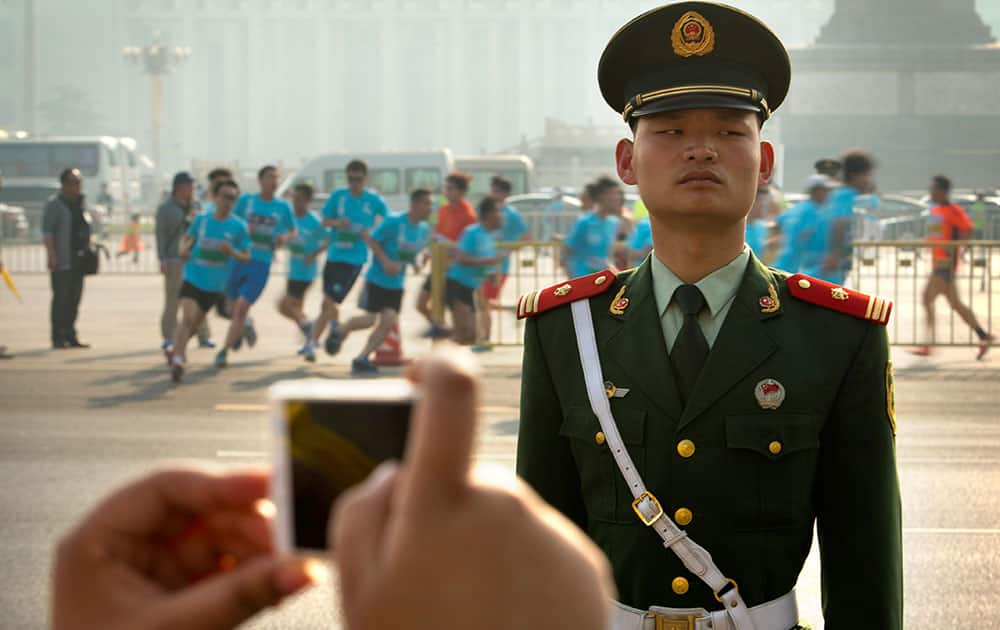 A spectator takes a photo of runners in a 10-kilometer (6.25 mile) road race as a Chinese paramilitary policeman stands guard near Tiananmen Square in Beijing.