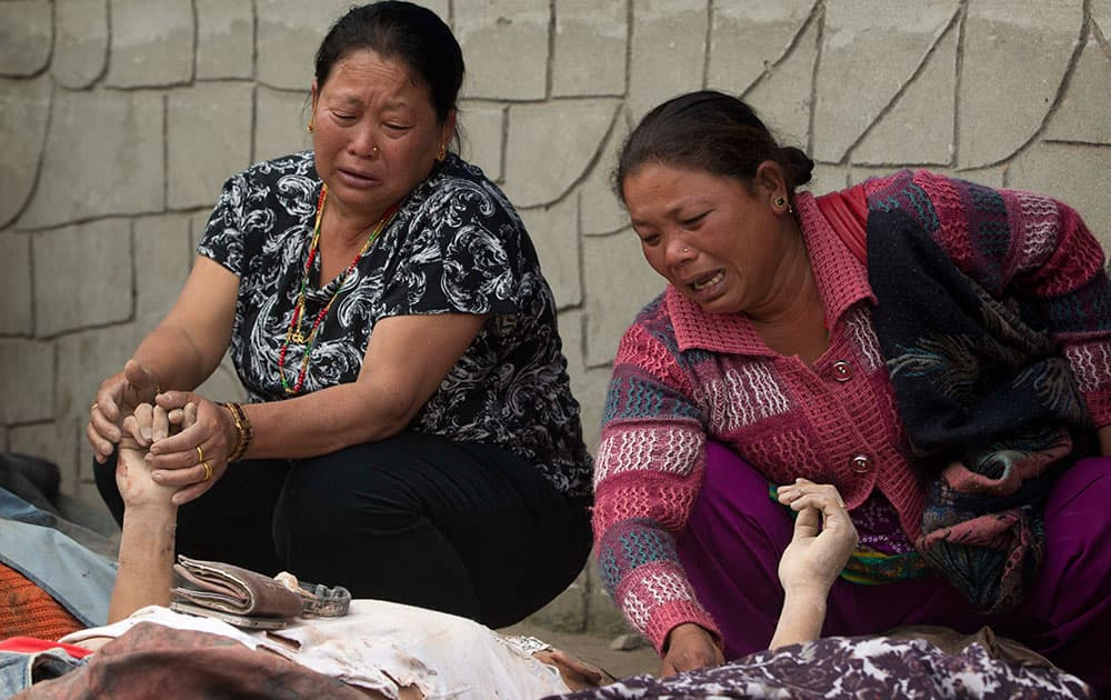 Unidentified relatives mourn near the bodies of those killed in earthquake at a hospital, in Kathmandu, Nepal, Sunday, April 26, 2015.