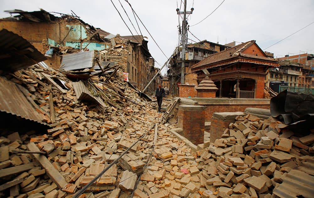 A Nepalese man walks through destruction caused by Saturday's earthquake, in Bhaktapur, Nepal, Sunday, April 26, 2015.