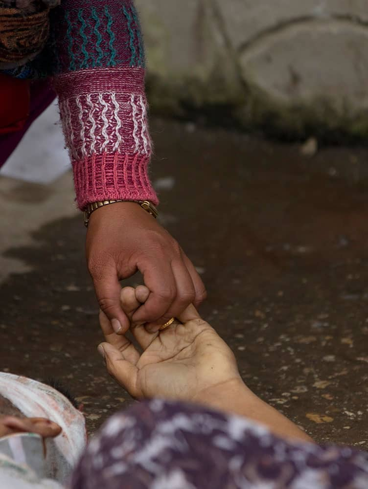 A Nepalese woman holds the hand of her relative killed in an earthquake at a hospital, in Kathmandu, Nepal, Sunday, April 26, 2015.
