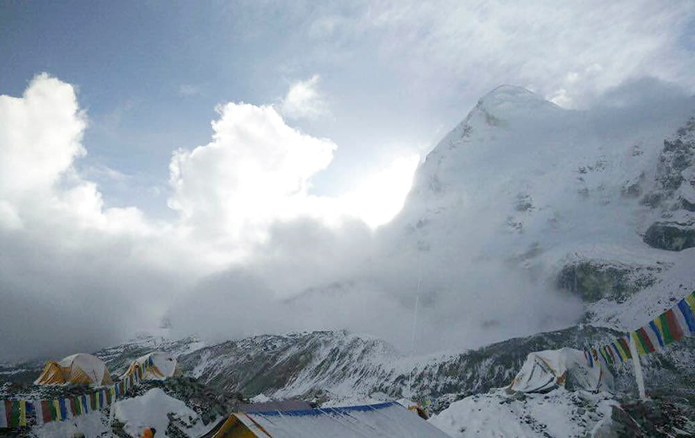 This photo provided by Azim Afif, shows a small avalanche on Pumori mountain as seen from Everest Base Camp, Nepal.