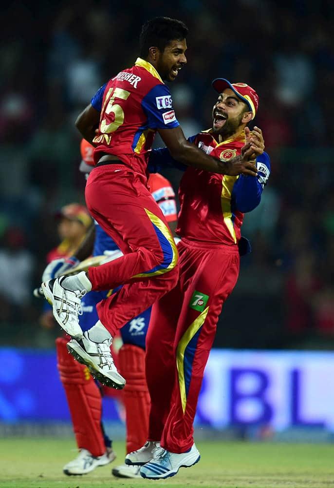 Royal Challengers Bangalore captain Virat Kohli and bowler Varun Aaron celebrate wicket of Delhi Daredevils batsman A Mathews during an IPL match at Feroz Shah Kotla Stadium in New Delhi.