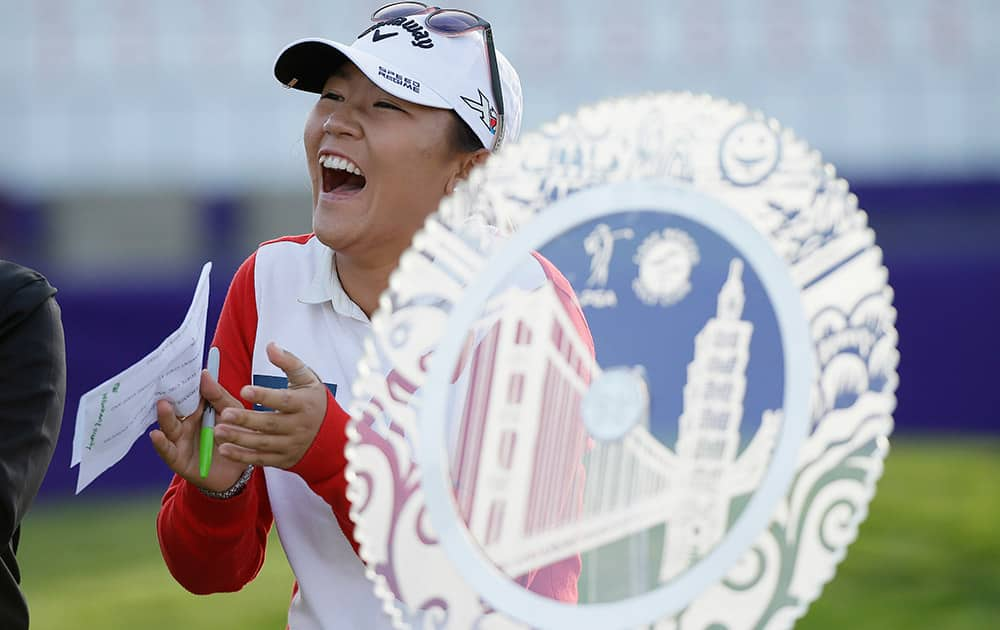 Lydia Ko of New Zealand laughs standing by her trophy after winning the Swinging Skirts LPGA Classic golf tournament, in Daly City, Calif.