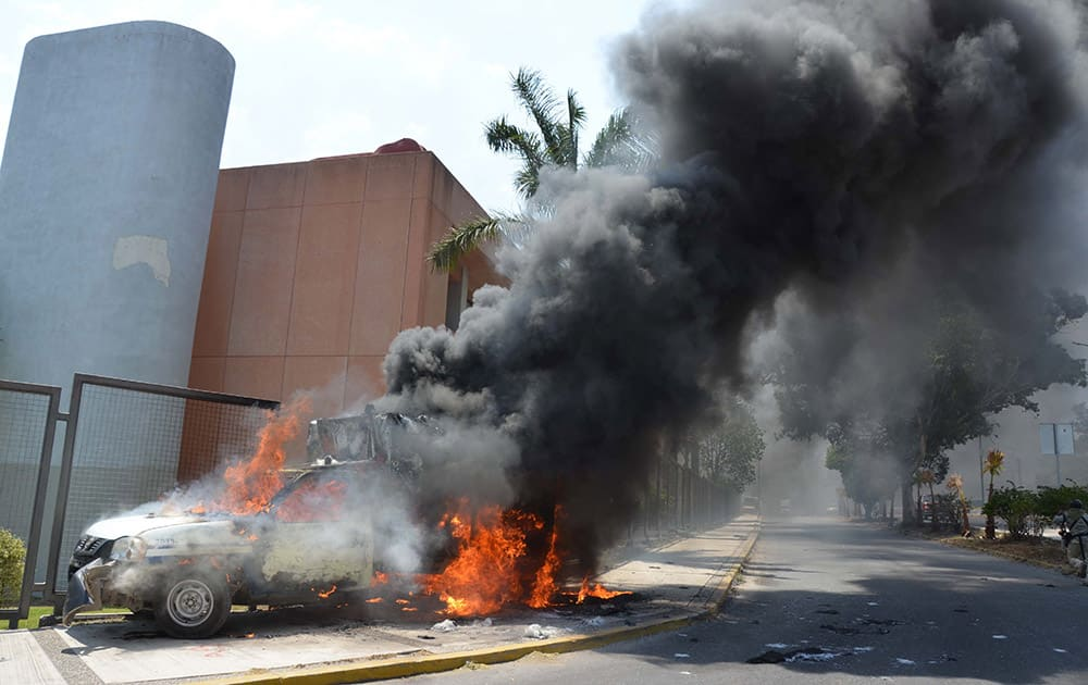 A truck that was torched by protesters burns near the main entrance of the state congress building in Chilpancingo, Mexico.