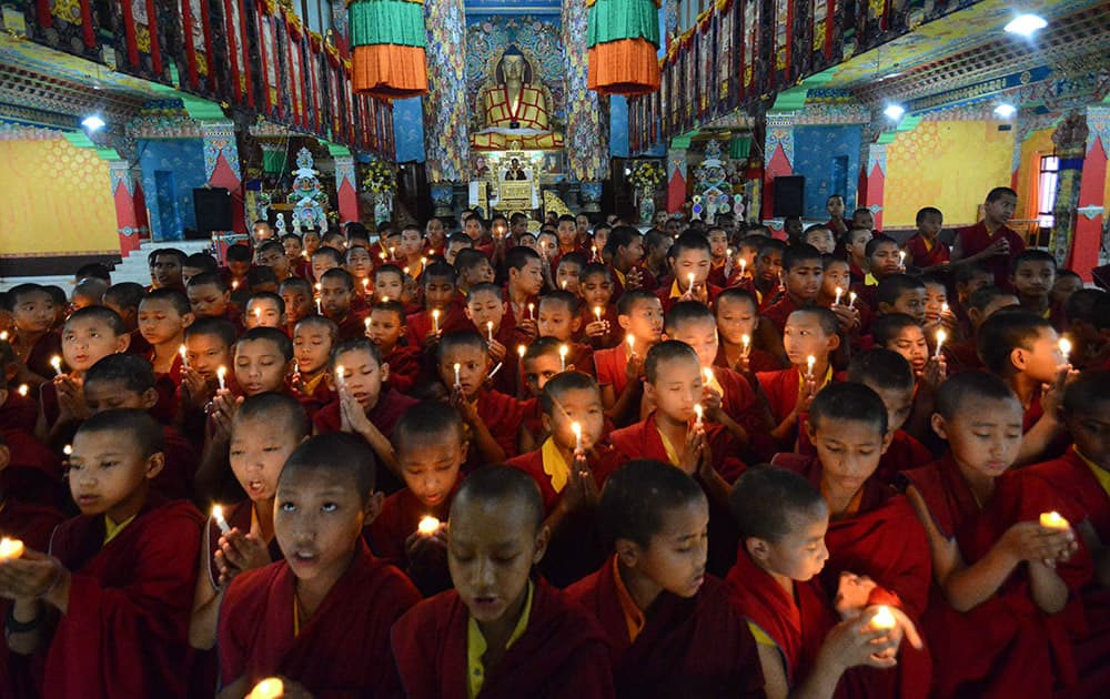 Novice Buddhist monks light candles and offer prayers for victims of Nepal's earthquake, in Bodhgaya, India.