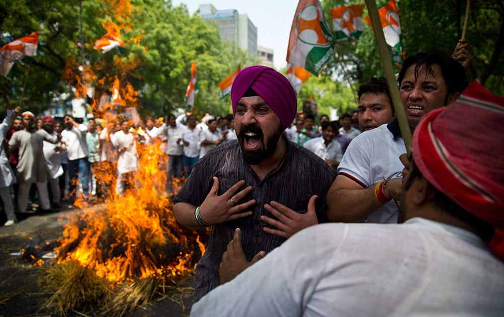 Farmers and Youth Congress party activists burn destroyed wheat as they protest against the government in New Delhi, India.