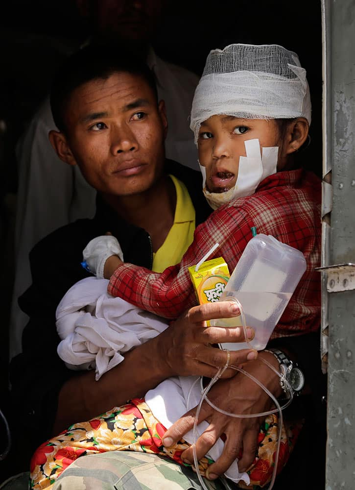 A child injured in Saturday's earthquake, is carried by a Nepalese soldier after being evacuated as they wait to disembark from an Indian Air Force helicopter at the airport in Kathmandu, Nepal.