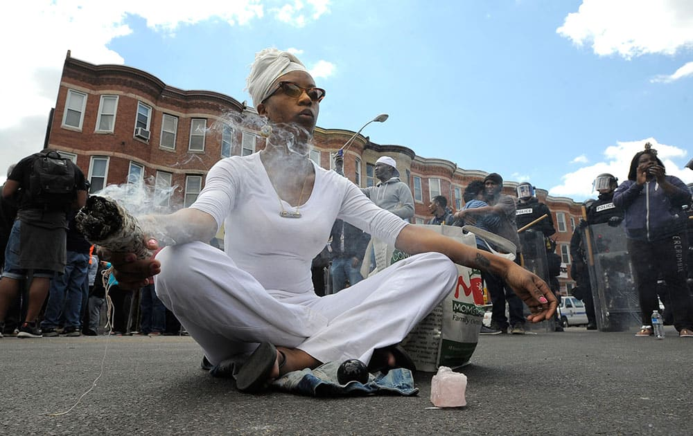 Shawna Murray-Browne sits in a street in Baltimore. Maryland's governor vowed there would be no repeat of the looting, arson and vandalism that erupted Monday in some of the city's poorest neighborhoods.
