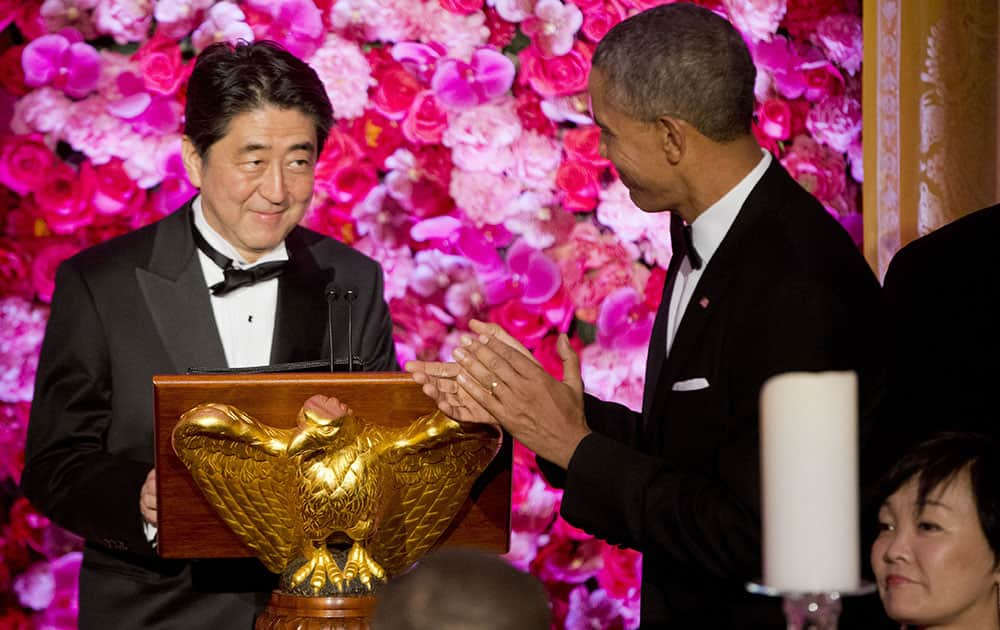 President Barack Obama introduces Japanese Prime Minister Shinzo Abe, left, as he host him and Abe's wife Akie Abe, right, at the State Dinner at the White House in Washington.