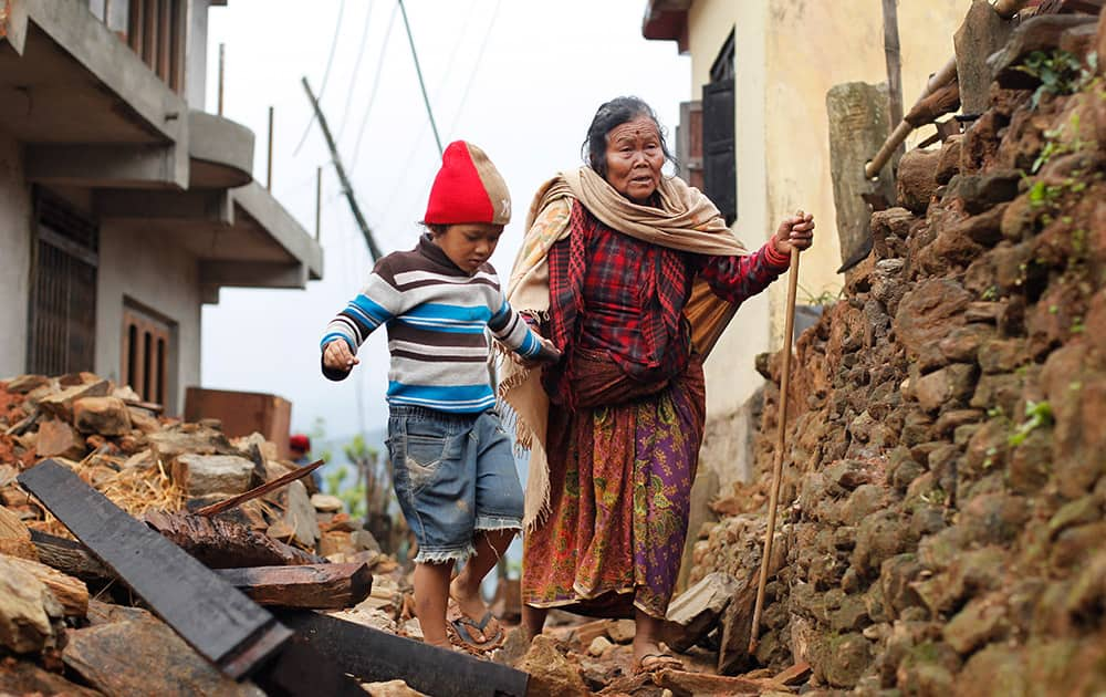 Jagot Kumari Rana, 79, is led through the rubble of collapsed homes by her grandson Sogat Rana, 7, in Paslang village near the epicenter of Saturday's massive earthquake in the Gorkha District of Nepal.