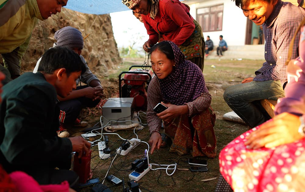 Young villagers giggle as they get the chance to charge their mobile phones from a generator in the destroyed village of Paslang near the epicenter of Saturday's massive earthquake in the Gorkha District of Nepal.