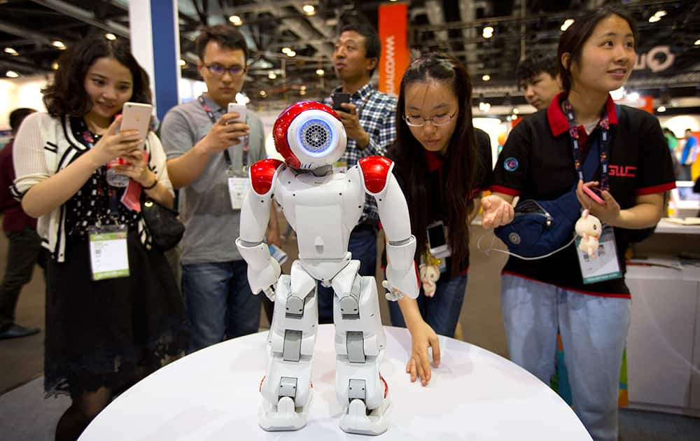 Visitors watch as a robot from Aldebaran Robotics dances at the Global Mobile Internet Conference in Beijing.