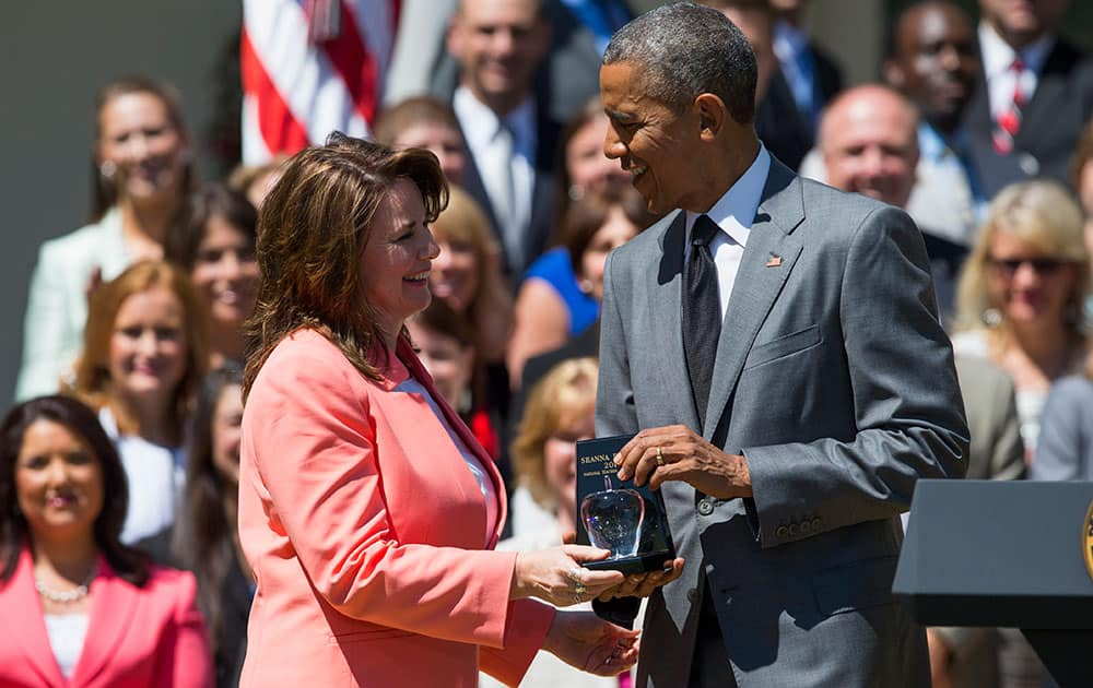 President Barack Obama presents an award to the National Teacher of the Year Shanna Peeples of Amarillo, Texas during an event to honor the teachers of the year, in the Rose Garden of the White House in Washington.