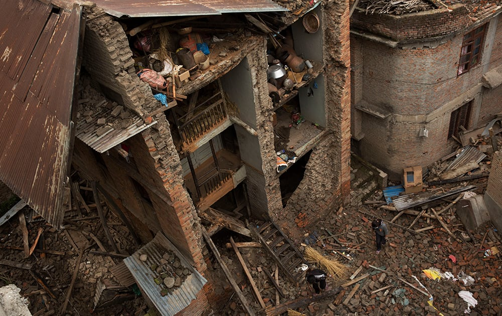People walk past a house with one side of its walls completely destroyed by Saturday's earthquake in Sakhu, on the outskirts of Kathmandu.