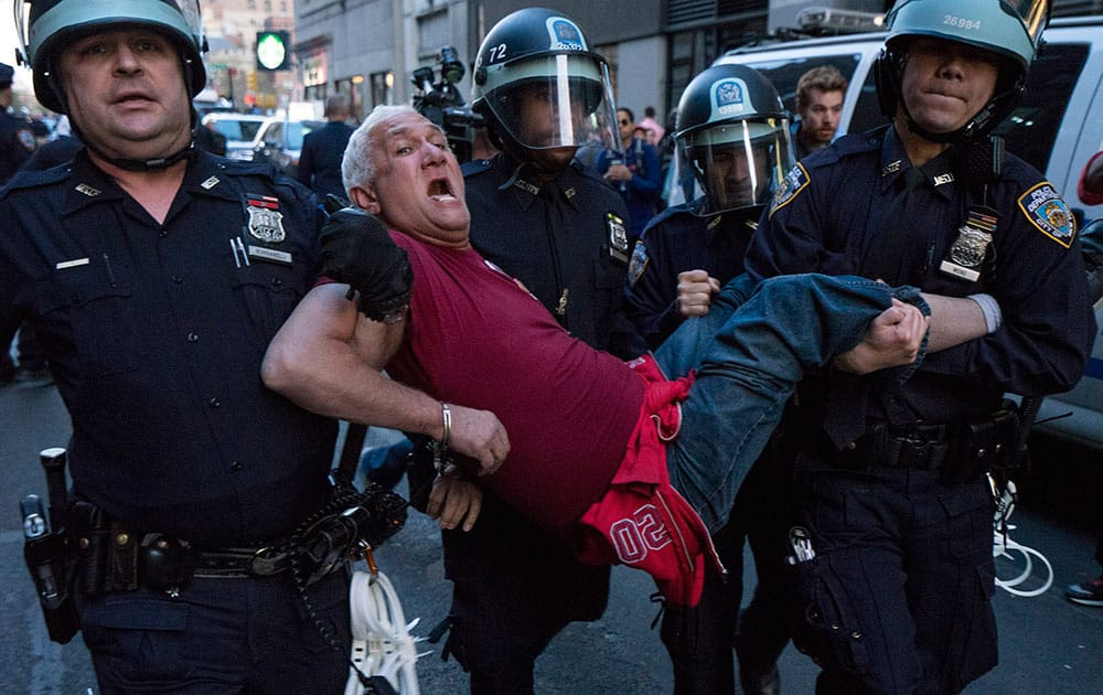 A man is carried by police officers as arrests are made at Union Square, in New York.
