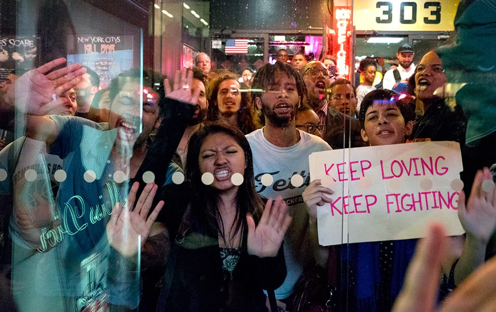 Protesters slam their hands against a bus shelter as they chant, in New York. People gathered to protest the death of Freddie Gray, a Baltimore man who was critically injured in police custody.