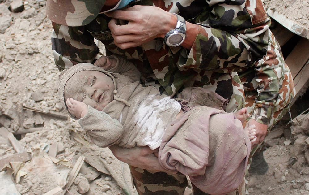 Four-month-old baby boy Sonit Awal is held up by Nepalese Army soldiers after being rescued from the rubble of his house in Bhaktapur, Nepal, after Saturday's 7.8-magnitude earthquake shook the densely populated Kathmandu valley.