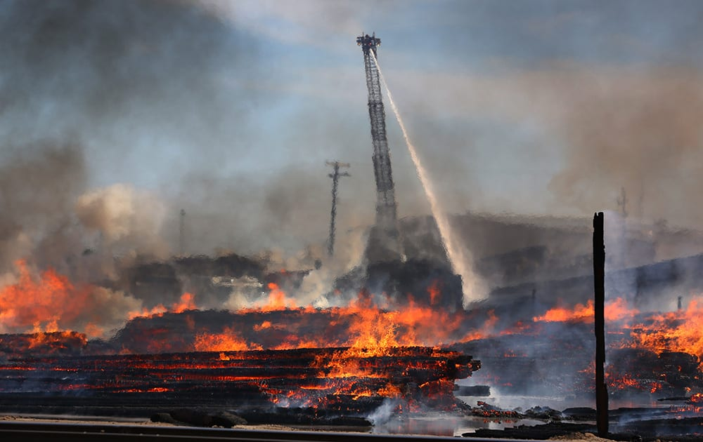 Fresno firefighters put water on a large scale fire that broke out at the McFarland Cascade utility yard, in Fresno, Calif.
