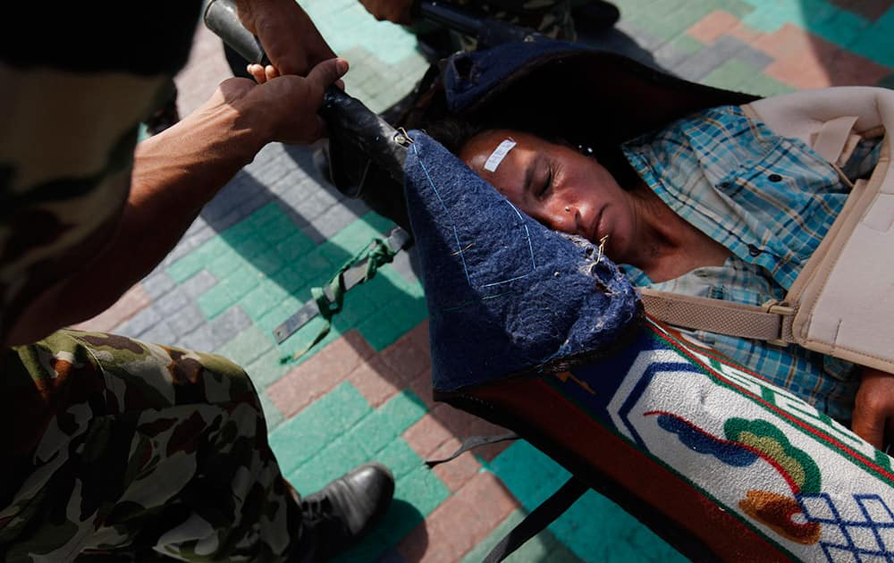 A woman, injured in Saturday's earthquake, is carried on a stretcher after being evacuated from Melamchi at Sindupalchowk district in an Indian Air Force helicopter, at the airport in Kathmandu, Nepal.