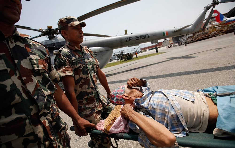 A man injured in Saturday's earthquake is carried on a stretcher after being evacuated in an Indian Air Force helicopter, in Kathmandu, Nepal.