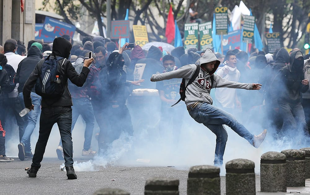 A protester kicks a teargas canister during a May Day march in Bogota, Colombia.