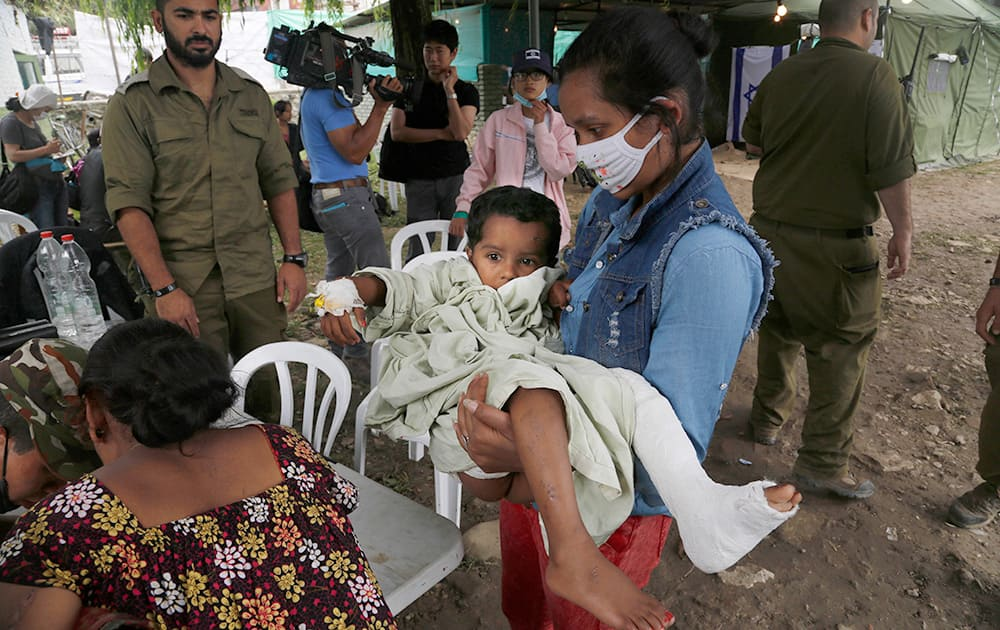 A relative carries a child injured in Saturday's earthquake, at the Israeli field hospital for further treatment in Kathmandu, Nepal.