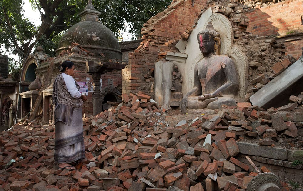 A Nepalese woman offers morning prayers at a temple damaged in last Saturday's earthquake in Bhaktapur, Nepal.