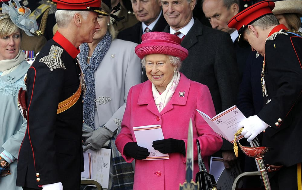 Britain's Queen Elizabeth II smiles during a visit to Richmond Castle to attend the amalgamation parade of The Queen's Royal Lancers and 9th/12th Royal Lancers, in Richmond, England. Earlier Saturday, Kate, The Duchess of Cambridge gave birth to a baby girl, that will now be fourth in line to the throne.