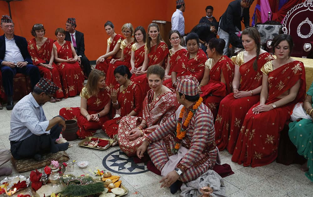Nepalese groom Dipesh Munakari, seated right & his French bride Eugenie Prouvost at their wedding ceremony. The couple have tied the knot determined to show that life goes on.