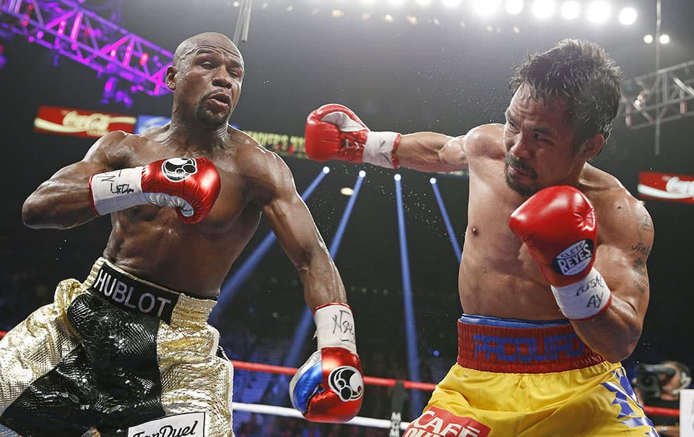 Manny Pacquiao, from the Philippines, right, throws a right against Floyd Mayweather Jr., during their welterweight title fight in Las Vegas.