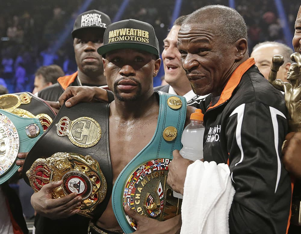 Floyd Mayweather Jr., left, poses with his champion's belts and his father, head trainer Floyd Mayweather Sr., after his victory over Manny Pacquiao, from the Philippines, in their welterweight title fight in Las Vegas.