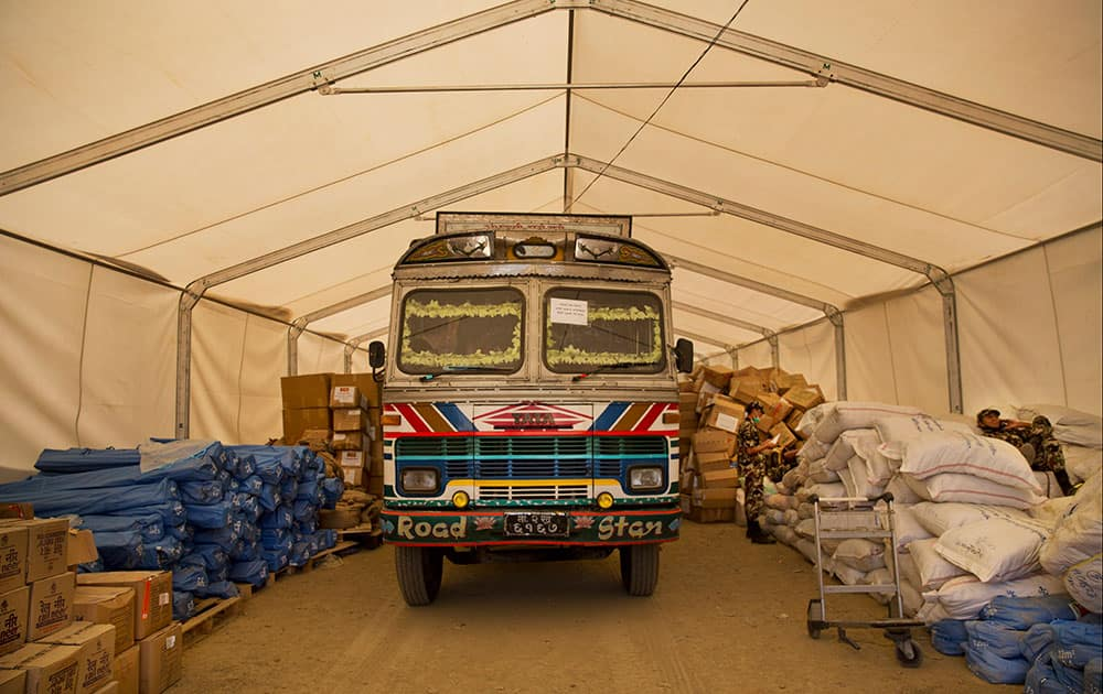 A Nepalese truck is surrounded by miscellaneous aid supplies at the cargo terminal of Tribhuvan International airport in Kathmandu, Nepal.