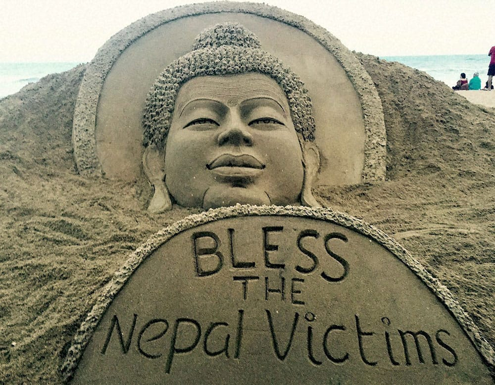 Sand artist Sudarsan Pattnaik creates a sand sculpture of Lord Budha with a message Bless the Nepal victims at Puri beach in Odisha.