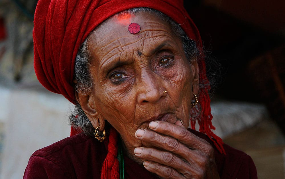 Tika Devi Khanal, 81, sits at her damaged home in the destroyed village of Pokharidanda, near the epicenter of the April 25 massive earthquake, in the Gorkha District of Nepal.
