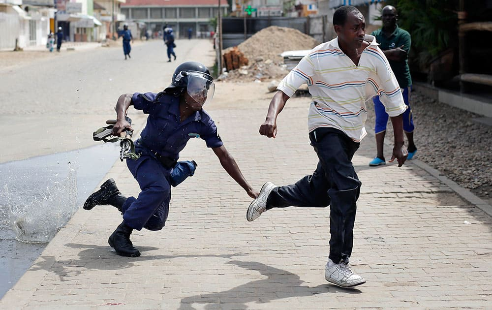 Riot police chase a demonstrator in Bujumbura, Burundi. Anti-government demonstrations resumed in Burundi's capital after a weekend pause as thousands continue to protest the president's decision to seek a third term.