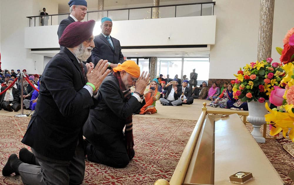 Prime Minister Narendra Modi kneels in reverence during his visit to Gurudwara Khalsa Diwan as his Canadian counterpart looks on in Vancouver.