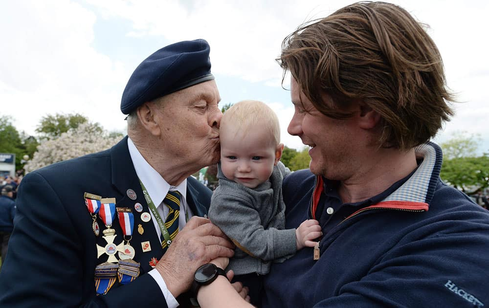 Canadian World War II navy veteran Bert Reynolds, 88, kisses six-month-old Siem Henken, held by his father during VE-Day celebrations in Wageningen, Netherlands.