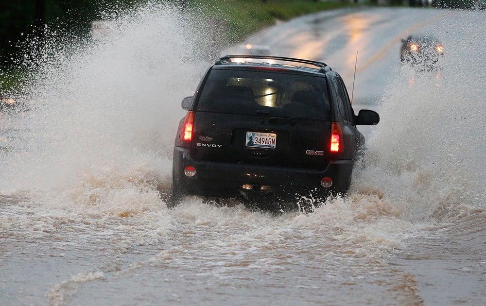 A vehicle makes its way through deep water following heavy rain in Moore, Okla.