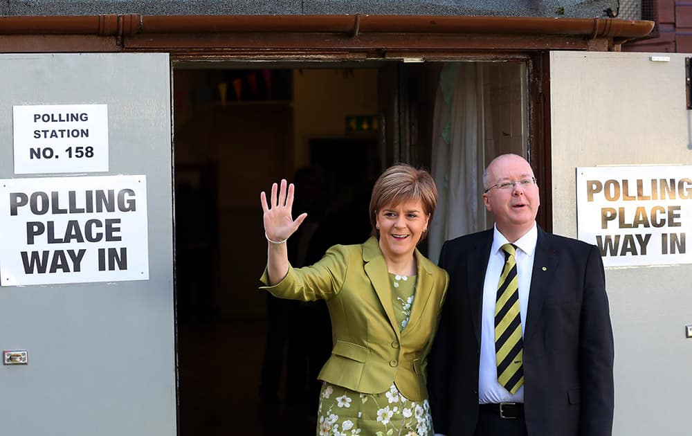 First Minister of Scotland and Scottish National Party leader Nicola Sturgeon and her husband Peter Murrell pose for photographs after casting her ballot at Broomhouse Community Hall in Broomhouse, Scotland.