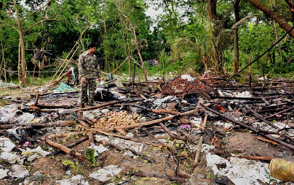 A Security officer investigates the site of a blaze at a firecracker factory in West Midnapore District, West Bengal. The blaze killed at least a dozen people, police said Thursday.