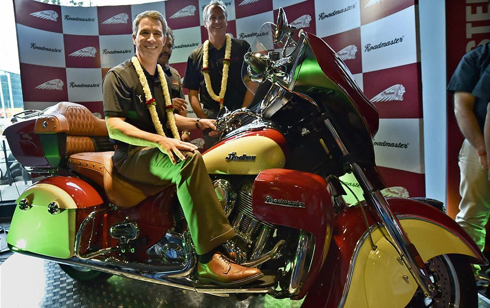 Polaris Industries Inc Chairman & CEO Scott Wine sitting on the bike as President & COO Bennet J Morgan looks on during the launch of the Indian Roadmaster and Indian Chief Dark Horse, luxurious American bike brand in Bengaluru.
