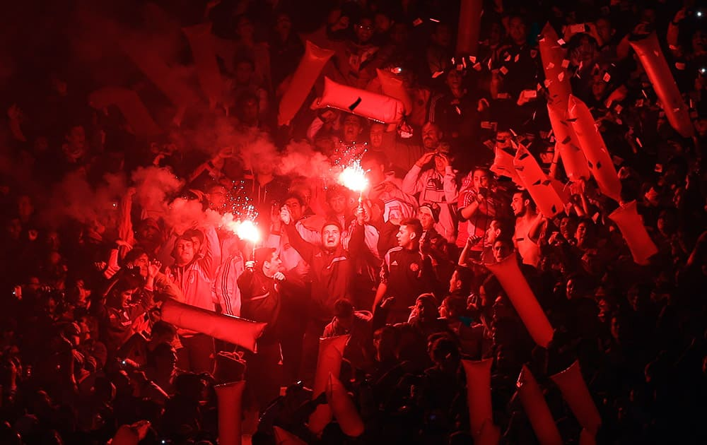 River Plate fans light a flare before the start of a Copa Libertadores soccer match against Argentina's Boca Juniors in Buenos Aires, Argentina.