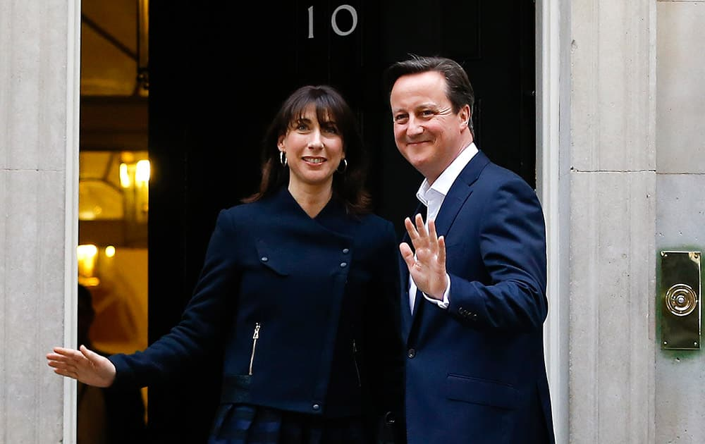 Britain's Prime Minister David Cameron and his wife Samantha return to 10 Downing Street in London. The Conservative Party surged to a surprisingly commanding lead in Britain's parliamentary election, with returns Friday backing an exit poll's prediction that Prime Minister David Cameron would remain in 10 Downing Street.