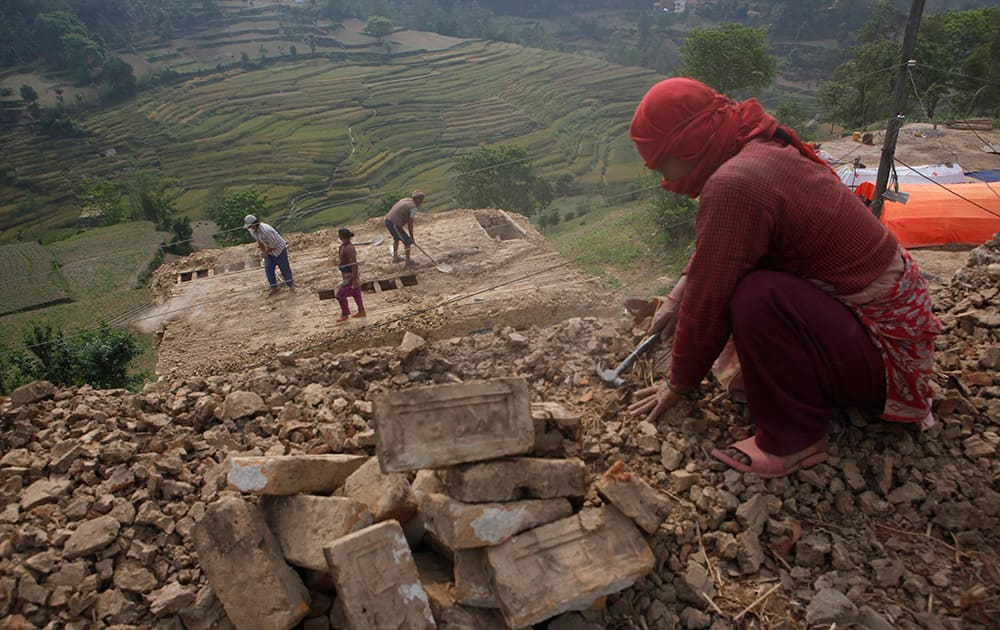 Nepalese people work to rebuild their damaged homes in Lalitpur, Nepal.