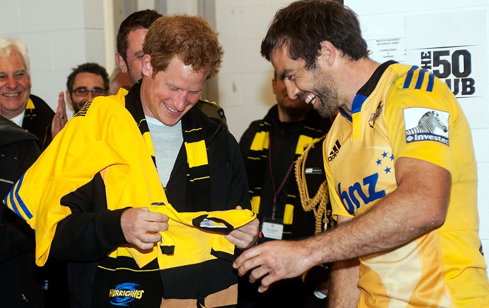 Hurricanes captain Conrad Smith presents Britain's Prince Harry with a personalized onesie for his brother Prince William's daughter, Princess Charlotte in the Hurricanes changing rooms after the Super Rugby against the Sharks at Westpac Stadium in Wellington, New Zealand.