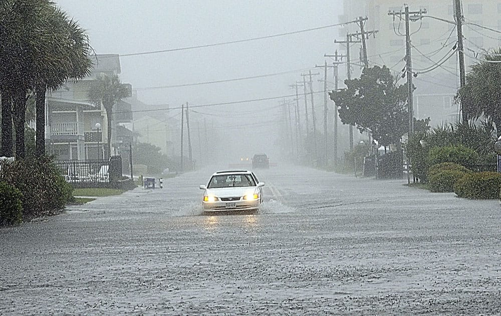 A car drives south on a flooded Ocean Boulevard after it drove past barricades warning of the high water, in North Myrtle Beach, S.C.