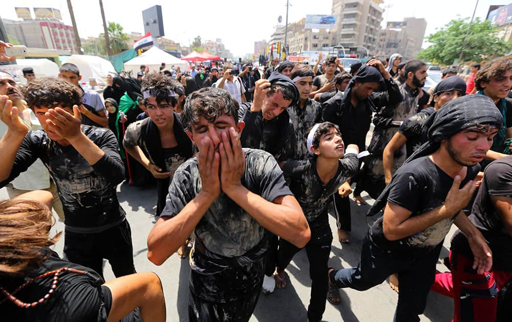Shiite pilgrims beat themselves and cover themselves with mud as they march toward the Imam Mousa al-Kazim shrine to commemorate the anniversary of the imam's death in Baghdad, Iraq.