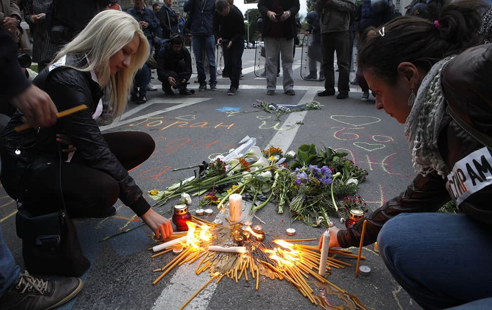 People light candles and lay flowers as police officers stand guard in front of the Government building in Skopje, Macedonia.